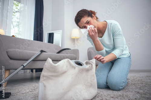 Obraz Safety violation. Adolescent woman being prone to dust allergies suffering from consequences of not wearing any personal protective equipment while cleaning dirty carpet - fototapety do salonu