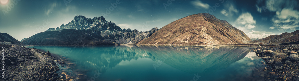 Fototapeta Spectacular scenery the crystal clear Gokyo Lake on the mighty snow-covered Himalayas background. Strength and beauty of wild virgin nature. Ideal image for the backgrounds and wallpapers.