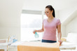 housework and household concept - happy woman or housewife spraying bath towel on ironing board at home