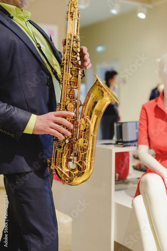 musician plays the saxophone performance at a concert in shopping center of wome Wallpaper Mural