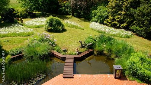 naturbelassener Gartenteich mit Brücke und Margeritenwiese an ...