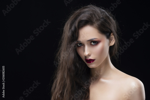 Portrait of a beautiful glamorous brunette girl with naked shoulders. Shimmering makeup, red lips.