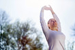 Leinwanddruck Bild - Morning gymnastics. Nice cheerful woman holding her hands up while doing morning exercises