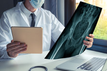 Doctor Watching A X-ray Of Bones Of Hips And Holding A Digital Tablet