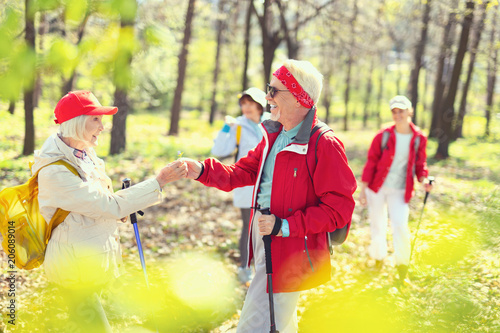 My gift. Cheerful aged man smiling and giving a flower to a woman while hiking