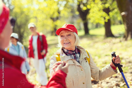 Fotobehang Zwavel geel I feel great. Inspired aged woman smiling and looking at the man while hiking