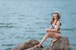 Portrait of beautiful asian sexy woman wear bikini on the rock side sea in the evening,Lifestyle of modern women,Thailand people