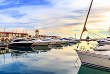 Luxury Yachts And Motor Boats At Sunset. Sailing Boats Docked At Pier In Marina In Sunshine.