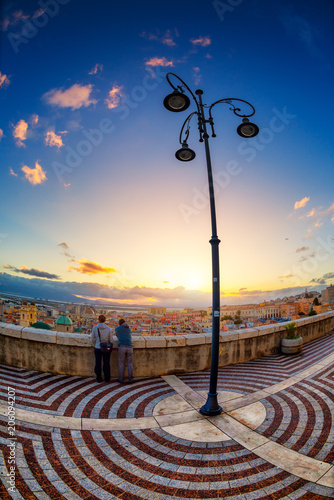 One couple of lovers looking at sunset on a bastion. Fototapete
