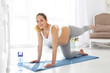 Safe yoga poses. Jovial pregnant woman staring at camera and trying yoga