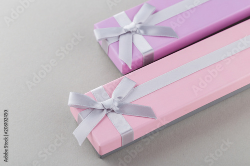 Fotografía  Pink and violet gift boxes with bows on gray background
