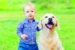 Leinwandbild Motiv Little boy child and Golden Retriever dog on the grass on the summer park
