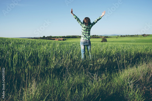 Fotografie, Obraz  Mujer disfrutando de un día soleado en el campo con los cultivos verdes
