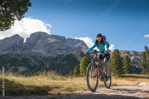 pretty young woman on bicycle in italien dolomites,  south tyrol, platzwiese Canvas Print