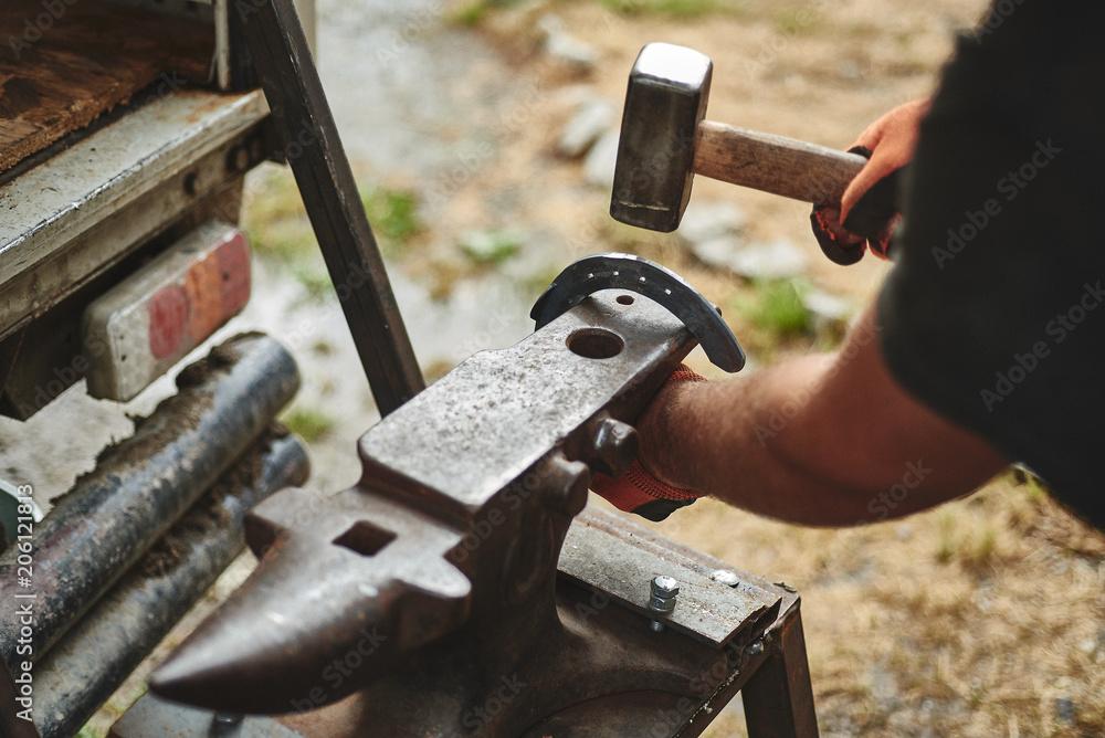 Fototapeta Kowal uderza młotem, formuje podkowę