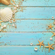 seashells on blue wooden background, summer frame
