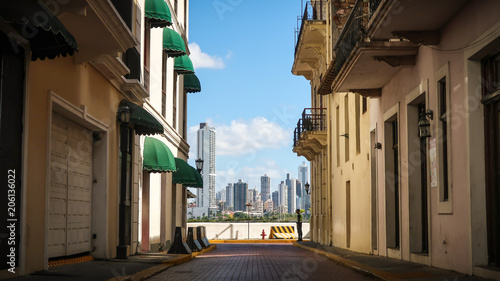 A colorful alley on a sunny day in the old town Casco Viejo with the skyline of Panama City in the background.