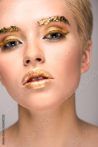Foto op Plexiglas Beauty attractive stylish woman with golden glitter on face looking at camera isolated on grey