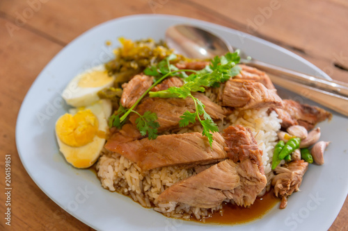 Popular Thai food of Stewed pork leg on rice on wooden table.