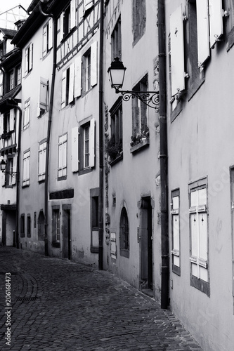 Poster Smal steegje Narrow alley with cobbled street. Black and white image.