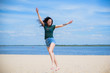 Woman Jumping on the Beach Having Fun, Summer vacation holiday Lifestyle. Happy women jumping freedom on white sand.
