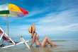 woman relax comfortable sitting in water at middle part of sea under multicolor beach gamp umbrella at lowest tide with deck couch beach chair enjoy holidays and weekend vacation in summer time