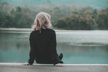 Teenager Girl Sitting Alone In The Park On Moutain Background With Copy Space.