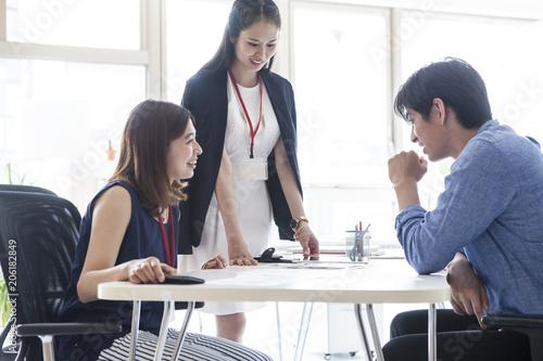 Obraz 明るいオフィスで会議をしている会社員たち - fototapety do salonu