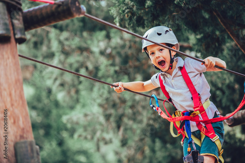 Fotografia  Little boy climbing in adventure activity park with helmet and safety equipment