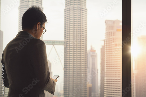 Fotografía  Malaysian business man contact to customer by wifi and smart phone in hotel room