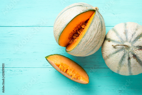 Cantaloupe melons on aquamarine background