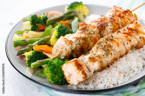 Fotografía  Chicken skewers with steamed vegetables and long rice