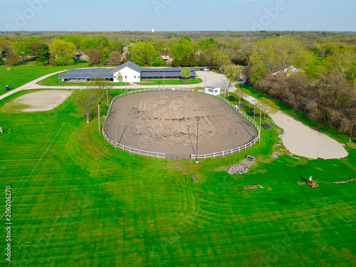 Photo Stands Green A person mowes the grass at a horse farm and equestrian center on a summer day