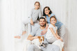 Friendly family of four memebers: cheerful European brunette female, her husband, two daughters and favourite pet, have good relationships, support each other. Affectionate parents with children