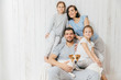 Horizontal shot of friendly family pose together against white background: two little sisters, father, mother and their pet. Happy parents and their female children. Family of four. Parenthood