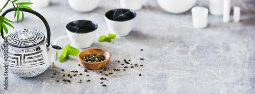 Photo sur Toile The White Iron Asian Teapot With Green Mint Leaves. Tea Time