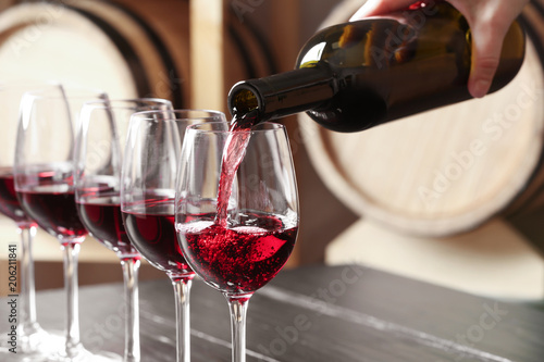 Woman pouring delicious red wine into glass, closeup