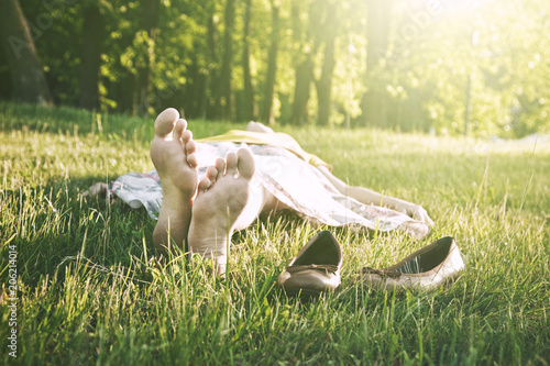 Photo girls legs lying in grass barefoot without shoes