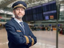Pilot In Der Uniform Mit Goldenen Streifen Und Kappe Kreuzte Seine Arme Beim Stehen Im Flughafen