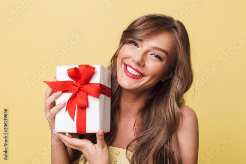Poster Ecole de Danse Photo of caucasian pleased woman 20s having long brown hair smiling and holding present box wrapped with bow, isolated over yellow background