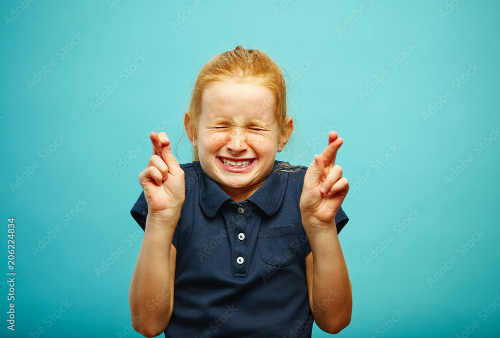 Fototapety, obrazy: Children girl tightly closed his eyes and put fingers crossed, make a wish, believe in the dream, expresses heartfelt emotions, has funny facial features, beautiful red hair with freckles.