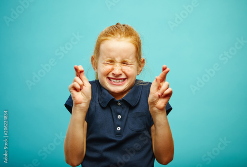 Photographie  Children girl tightly closed his eyes and put fingers crossed, make a wish, believe in the dream, expresses heartfelt emotions, has funny facial features, beautiful red hair with freckles