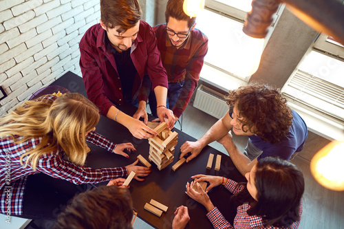 Fotografie, Tablou  Top view friends play indoor board games.