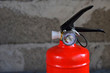 Compact red fire extinguisher for auto or home on grey background. For fire emergencies.