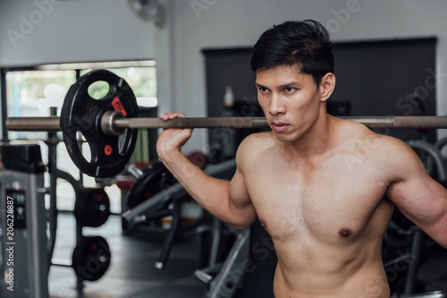 Foto op Plexiglas Fitness Muscular man working out in gym doing exercises with barbell at biceps, strong male.