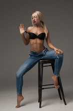 Beautiful And Sexy Blonde Woman Wearing Lingerie And Jeans