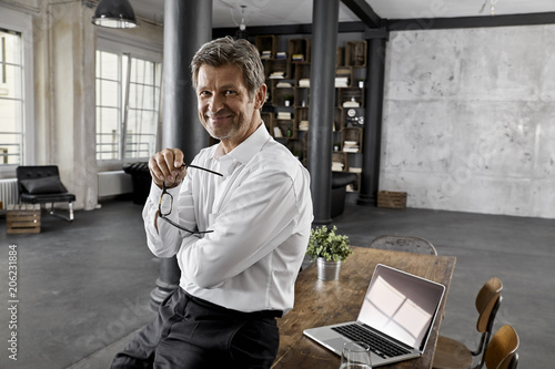 Portrait of mature business man in loft office