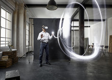 Mature Man With Vr Glasses Light Painting In Front Of Black Backdrop In Loft