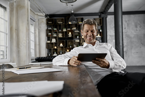 Portrait of mature business man using tablet computer in loft office