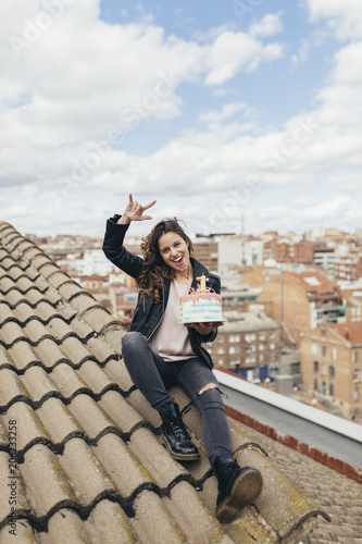 Laughing woman sitting on roof with Birthday cake showing Rock And Roll Sign